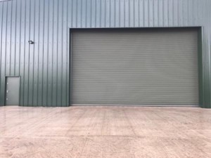 front of large bespoke hanger roller shutter and personnel access door